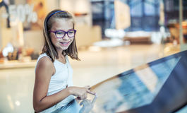 Beautiful cute little girl studying orientation plan in shopping mall. Shopping Center Store Guide. Modern touch screen technology. Toned image Royalty Free Stock Photo