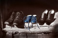 Beautiful cute nice shoes family Father mother shoes boots and baby child blue color old fashion shoes standing on old worn wood. Beautiful cute nice shoes stock photography
