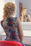 Beautiful cute happy girl with dyed hair krasivay and primp in the mirror Stock Photo
