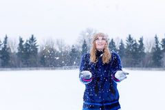 Beautiful cute sexy playful happy young woman in a blue coat in the cap playing with snow in the park Stock Photography