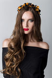 Beautiful cute skinny girl with long hair with a wreath on his head and bright make-up in elegant black dress with bare shoulders Stock Photo