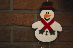 The beautiful cute small snowman decoration. On the brick wall background with negative space for texts Royalty Free Stock Photos