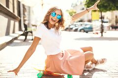 Beautiful cute smiling blond teenager model in summer hipster clothes. Sitting on orange penny skateboard on the street background. Surprise face, emotions stock photos