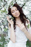 Beautiful cute sweet sexy girl bride with gentle eye make-up full lips in white light dress walks in the lush garden on warm s Royalty Free Stock Image