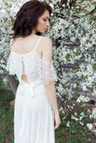 Beautiful cute sweet sexy girl bride with gentle eye make-up full lips in white light dress walks in the lush garden on warm s Stock Images