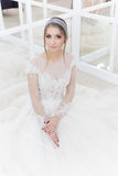 Beautiful cute tender young girl bride in wedding dress in mirrors with evening hair and gentle light make-up Royalty Free Stock Photos