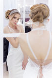Beautiful cute tender young girl bride in wedding dress in mirrors with evening hair and gentle light make-up Stock Images