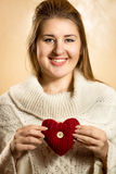 Beautiful cute woman posing with knitted heart Royalty Free Stock Images