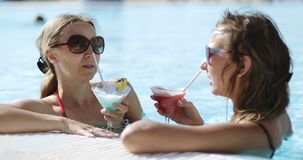 Beautiful cute women swims in a pool with clear blue water and drinks a colorful blue red yellow cocktail.