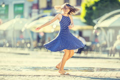 Beautiful cute young girl dancing on the street from happiness.Cute happy girl in summer clothes dancing in the sun Stock Photo