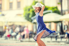 Beautiful cute young girl dancing on the street from happiness.Cute happy girl in summer clothes dancing in the sun.  royalty free stock images