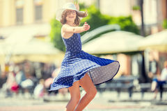 Beautiful cute young girl dancing on the street from happiness.Cute happy girl in summer clothes dancing in the sun.  stock photo
