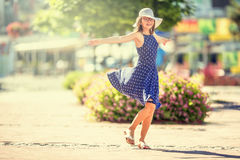 Beautiful cute young girl dancing on the street from happiness.Cute happy girl in summer clothes dancing in the sun Royalty Free Stock Photos