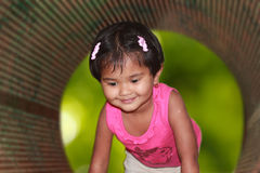 Beautiful & cute young girl kid smiling & playing in a park Stock Photo