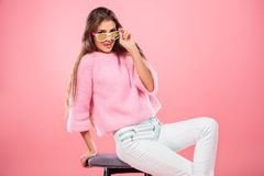 Smiling fashionable girl. A beautiful and cute young lady posing over pink background. Fashion concept royalty free stock photography