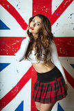 Beautiful Cute young Woman posing with the UK Flag in the backgr Royalty Free Stock Photos