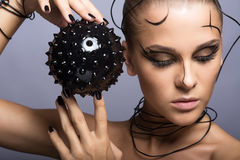 Beautiful cyber girl with black  prickly ball Stock Photos
