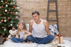 Dad and daughter, white t-shirt, blue jeans, gift box. Beautiful dad and daughter, has happy fun smiling face, dressed in white t-shirt, blue jeans, hold Royalty Free Stock Image
