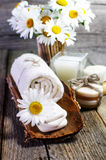 Beautiful daisies, candle, aromatic oils and other spa accessories on wooden surface. Royalty Free Stock Image