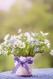 Beautiful daisy flowers in small decorative vase Stock Photo