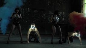 A beautiful dance of a group of people near smoke bombs. A beautiful dance of two girls and two men in gas masks near smoke bombs in an abandoned building stock video footage