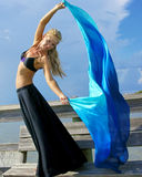 Beautiful dancer against sky. A beautiful sexy blonde belly dancer is looking towards viewer and leaning back holding her arms up  with her body twisted towards Stock Image