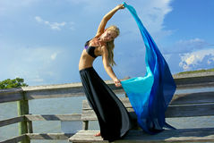 Beautiful dancer flowing cloth. A pretty blonde dancer making eye contact with her arms raised and her torso twisted towards the viewer, her long skirt and veil Royalty Free Stock Image