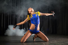 Beautiful dancer girl in a blue costume sitting. On the stage with smoke royalty free stock photos