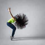 Beautiful dancer girl squatting with flying hair Royalty Free Stock Photos