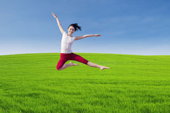 Beautiful dancer jumping above green field Royalty Free Stock Image