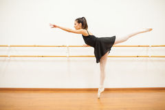 Beautiful dancer standing next to a barre Stock Photos
