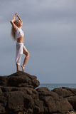 Beautiful Dancer stretching on lava rocks Royalty Free Stock Images