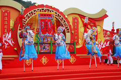 Beautiful dancers on stilts represent horsemen. The Chinese New year. A bright colourful concert of dancing folklore ensemble. Beautiful dancers on stilts Royalty Free Stock Photos