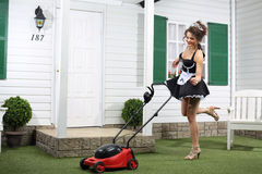 Beautiful dancing housemaid and lawn mower Royalty Free Stock Photo