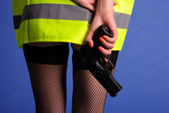 Beautiful and dangerous. Young woman in a warning vest holding a gun Royalty Free Stock Photography