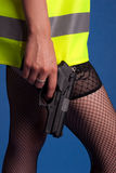 Beautiful and dangerous. Young woman in a warning vest holding a gun Stock Photography