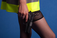 Beautiful and dangerous. Young woman in a warning vest holding a gun Stock Photo
