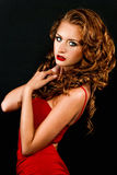 Beautiful, daring red-haired girl in a red dress Stock Images