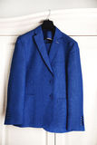 Beautiful dark blue grooms jacket. Hanging on white dresser Stock Photos