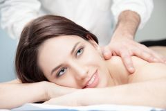 A beautiful dark hair woman doing a treatment pressure points ma. A dark hair woman having a massage by a physiotherapist doctor for a back and shoulder pain royalty free stock image