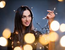 Beautiful dark hair young woman with blur lights. Beautiful dark hair young woman portrait, holding christmas lights. Beauty and fashion moody portrait, low stock photography