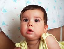 A beautiful dark haired and black eyed baby is watching in the distance royalty free stock image