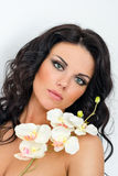Beautiful dark haired girl with orchids on white background Royalty Free Stock Images