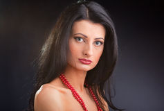 Beautiful dark haired girl with red beads Stock Images