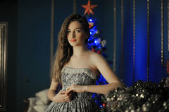 Beautiful dark-haired girl standing by the fireplace Royalty Free Stock Images