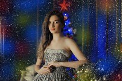 Beautiful dark-haired girl standing by the fireplace Stock Images