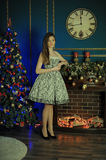 Beautiful dark-haired girl standing by the fireplace Stock Photo