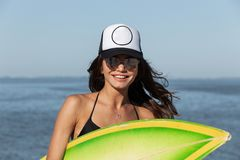 Beautiful dark-haired girl in sunglasses is holding in her hands a green surfboard near the sea. stock photography