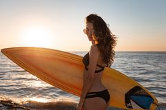 Beautiful dark-haired girl in a swimsuit and sunglasses holds a surfboard on the sandy beach on the sunset stock images
