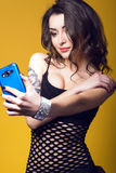 Beautiful dark haired girl with tattoo on her arm holding a blue cell phone and making selfie Stock Image